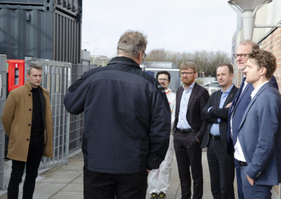 Outside the CBS1 facility, Steen B. Iversen is explaining to the visitors. Far left is the secretary to the minister and Daniele Castello, AAU, in the white protective suit. Credits: AAU